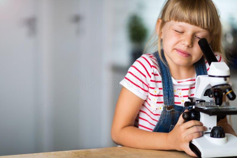 Flicka med mikroskopet arkivfoto