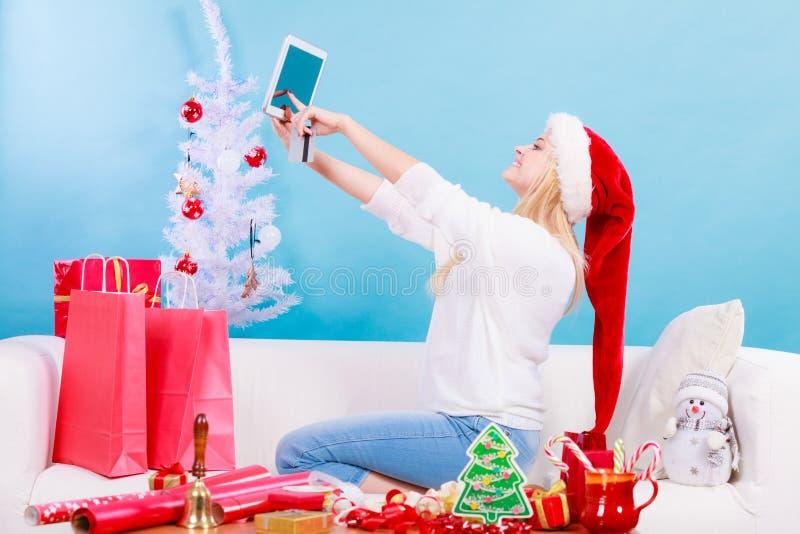 Flicka med minnestavlakreditkorten som g?r online-shopping royaltyfri foto