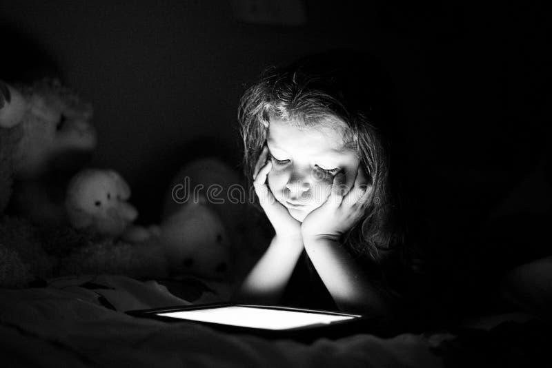 Flicka med minnestavlan i ett mörker arkivfoton
