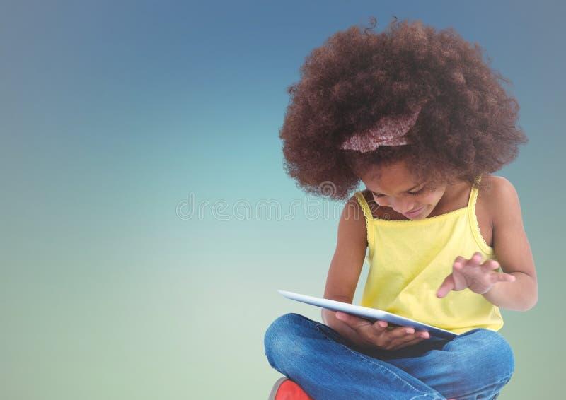 Flicka med minnestavlan mot bakgrund för blå gräsplan royaltyfri foto