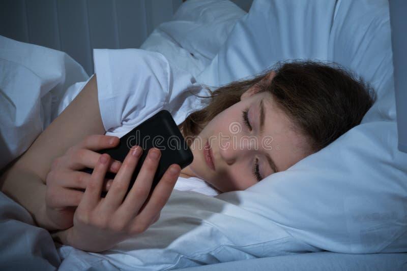 Flicka med mobiltelefonen på säng arkivfoton
