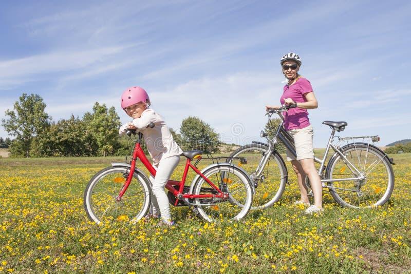 Flicka med modern på cyklar fotografering för bildbyråer