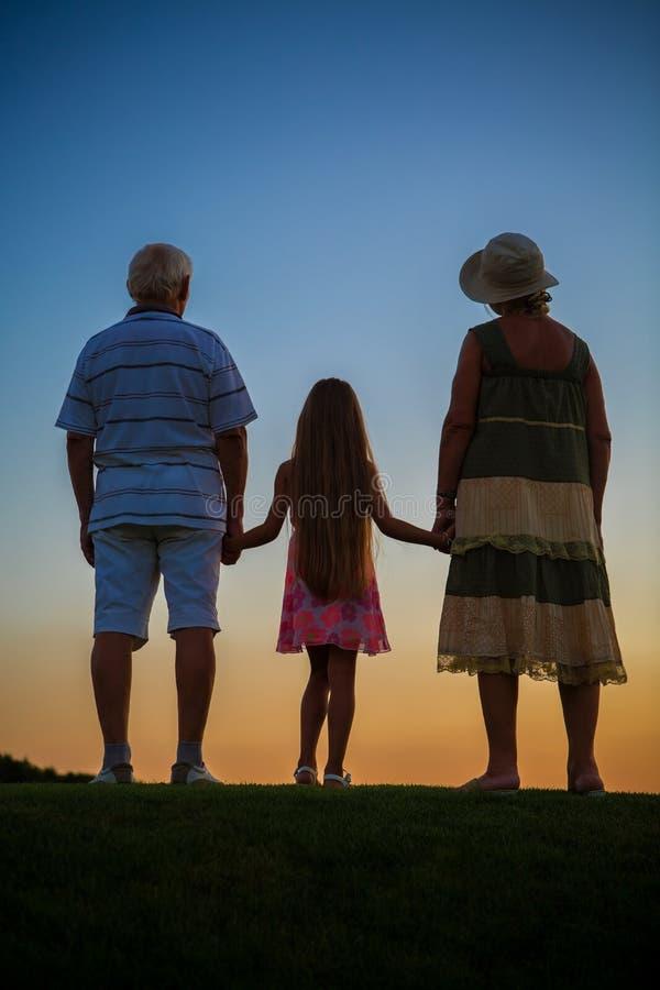 Flicka med morföräldrar, solnedgånghimmel royaltyfri bild