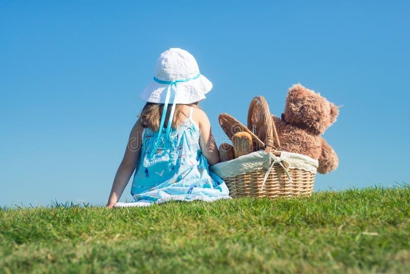 Flicka med nallebjörnen som har picknicken på gräs royaltyfria foton