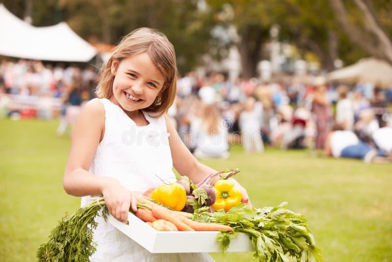 Flicka med ny jordbruksprodukter som köps på den utomhus- bondemarknaden arkivfoton