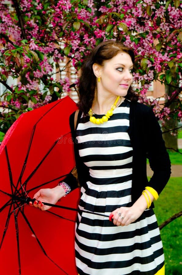 Flicka med paraplyet i de körsbärsröda blomningarna royaltyfria bilder