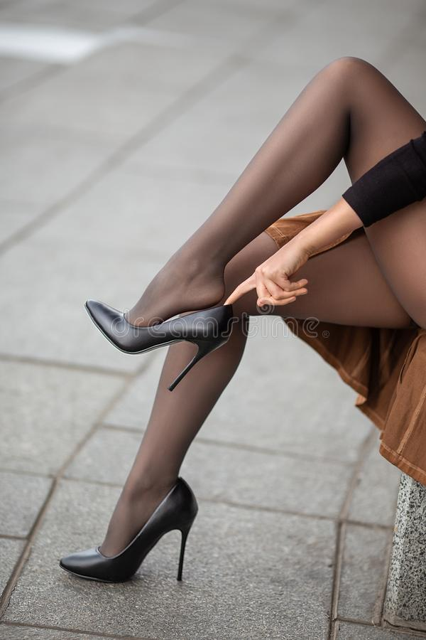 Flicka med perfekta ben i strumpbyxor på stadsfyrkanten arkivbilder