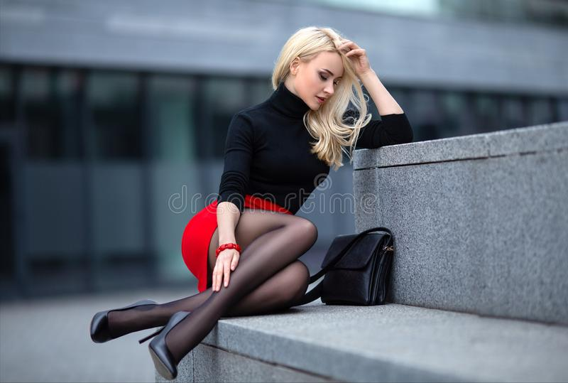 Flicka med perfekta ben i strumpbyxor p? stadsfyrkanten arkivbild