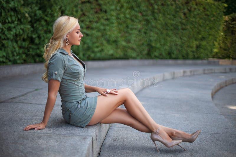 Flicka med perfekta ben som sitter på stadsfyrkanten royaltyfri bild