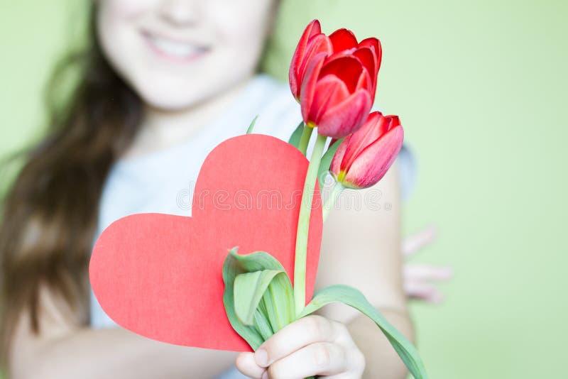 Flicka med röd hjärta och begrepp för dag för blommaberömmödrar royaltyfria bilder