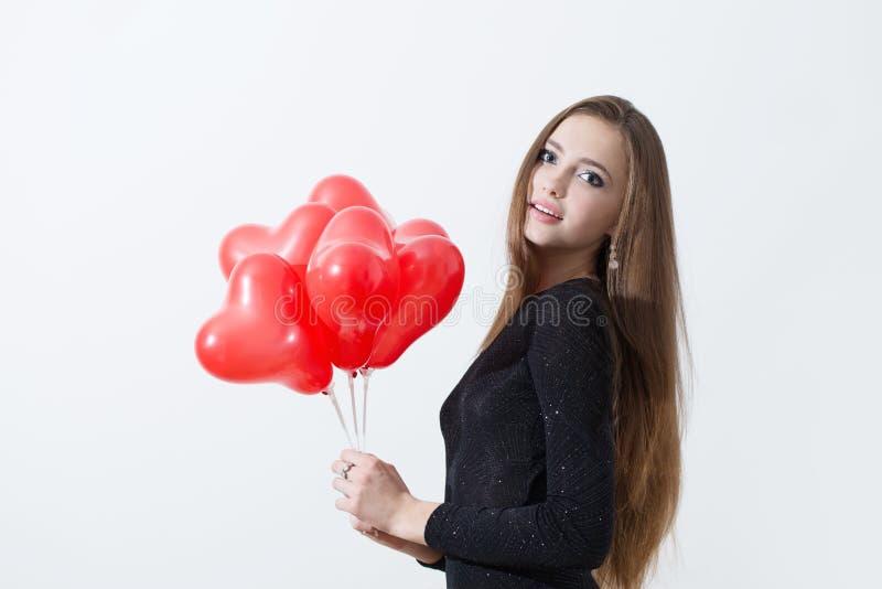 Flicka med röda ballonger på vit bakgrund arkivbilder