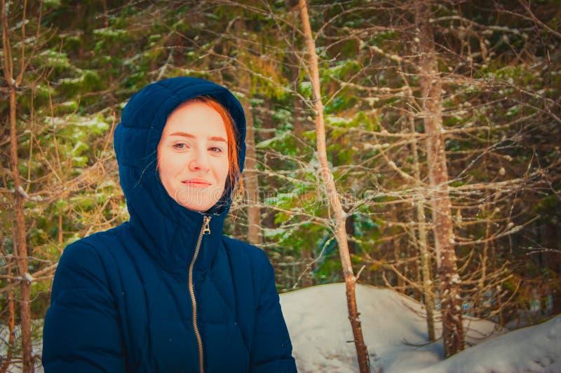 Flicka med rött hår i en huv i vinterskogen royaltyfri bild