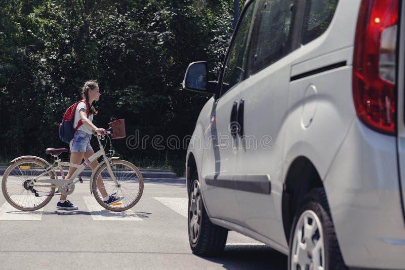 Flicka med ryggsäcken och cykeln på övergångsställe arkivfoton