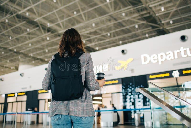Flicka med ryggsäcken på flygplatsen för avvikelse royaltyfri foto