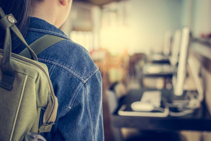 Flicka med ryggsäcken som skriver in till datorklassrumet royaltyfri bild