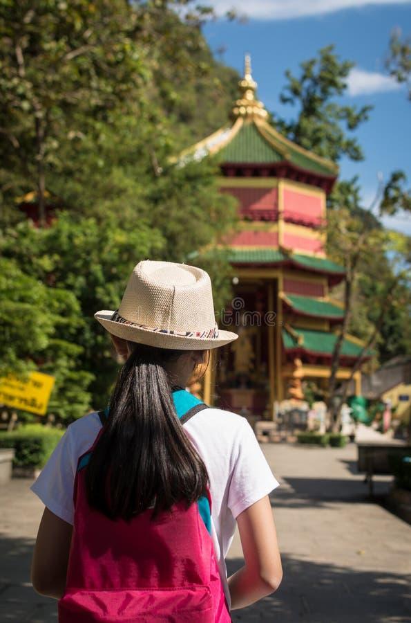 Flicka med ryggsäcken som skriver in till Quan Yin Shrine arkivbild