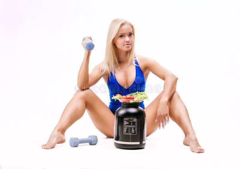 Flicka med sallad, en can av ett protein och hantlar arkivfoto