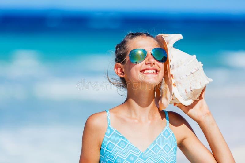 Flicka med skalet på stranden fotografering för bildbyråer