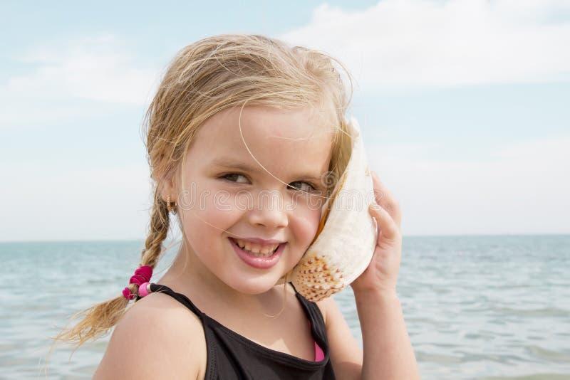 Flicka med skalet som lyssnar till havet royaltyfria foton
