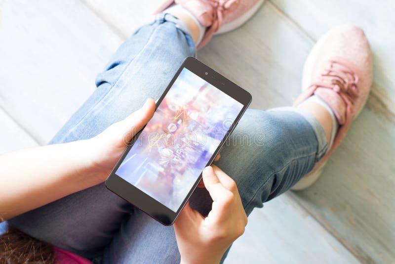 Flicka med smartphonebarn och teknologibegrepp arkivfoton