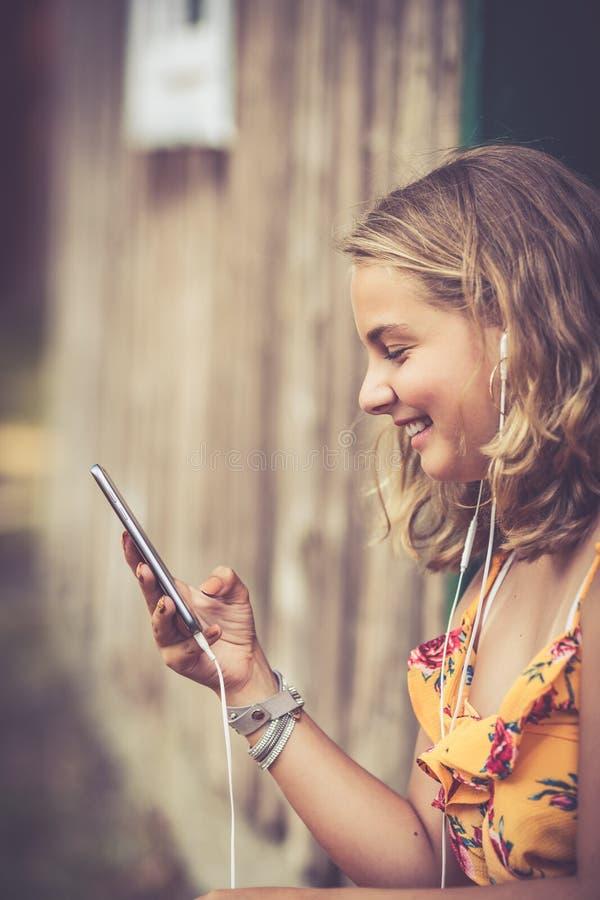 Flicka med smartphonen utomhus arkivfoto