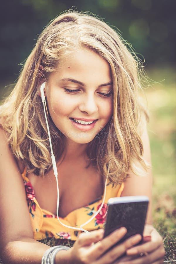 Flicka med smartphonen utomhus fotografering för bildbyråer