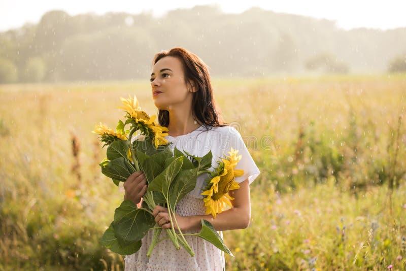 Flicka med solrosor i regnet arkivfoton