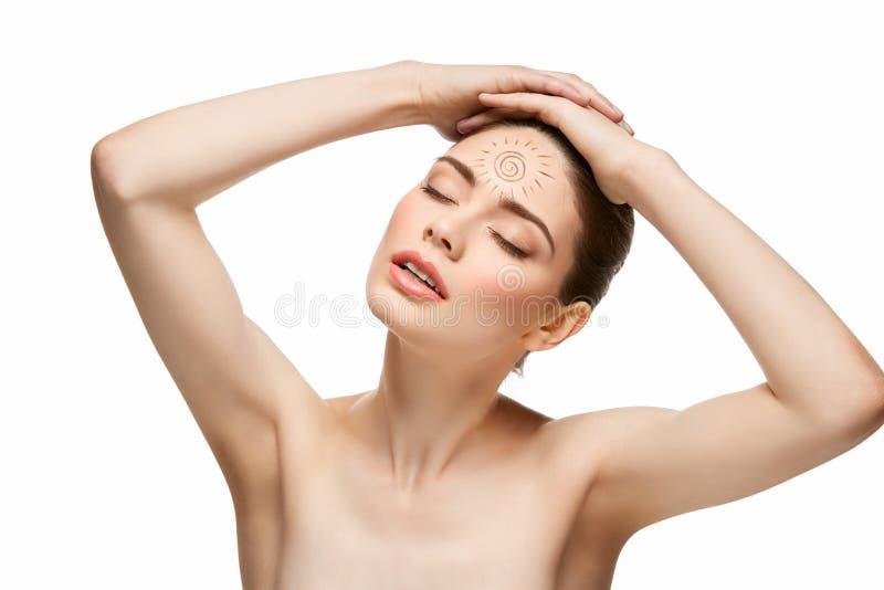 Flicka med solteckningen på pannan som isoleras på vit arkivfoto