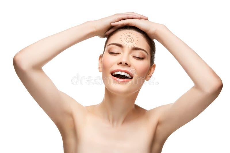 Flicka med solteckningen på pannan som isoleras på vit royaltyfri fotografi