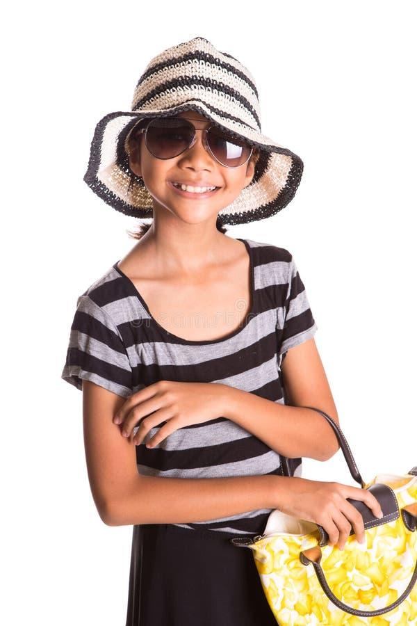 Flicka med sommarhatt, solglasögon och handväska X arkivfoto