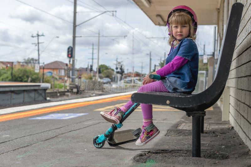 Flicka med sparkcykeln på drevstation 12 arkivfoto