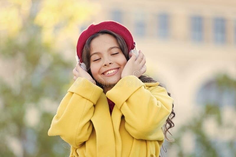Flicka med stads- bakgrund f?r h?rlurar Positiv p?verkan av musik Dr?kt f?r stil f?r barnflicka som fransk tycker om musik royaltyfri bild