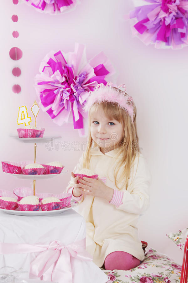 Flicka med stycket av kakan på det rosa garneringfödelsedagpartiet arkivfoton