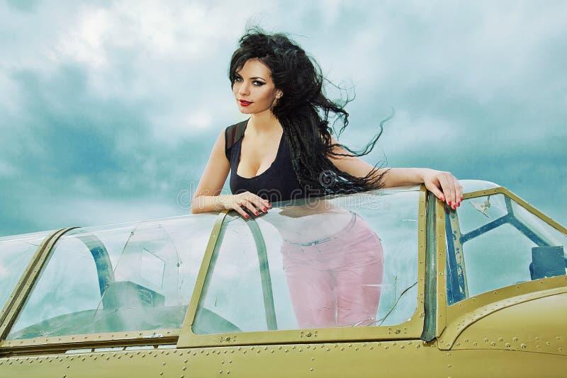 Flicka med svart långt hår med flygplanet fotografering för bildbyråer