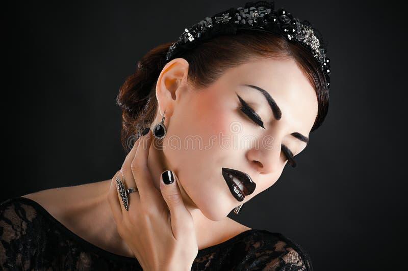 Flicka med svart makeup arkivbilder