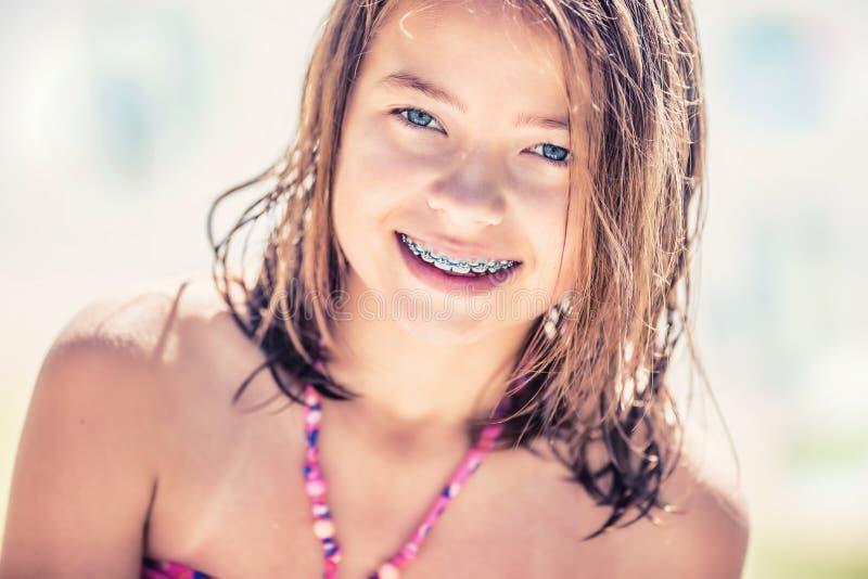 Flicka med tandhänglsen Nätt ung tonårig flicka med tand- hänglsen Stående av en gullig liten flicka på en solig dag i bikini arkivbild
