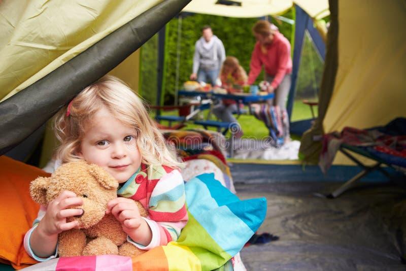 Flicka med Teddy Bear Enjoying Camping Holiday på campingplats royaltyfria bilder