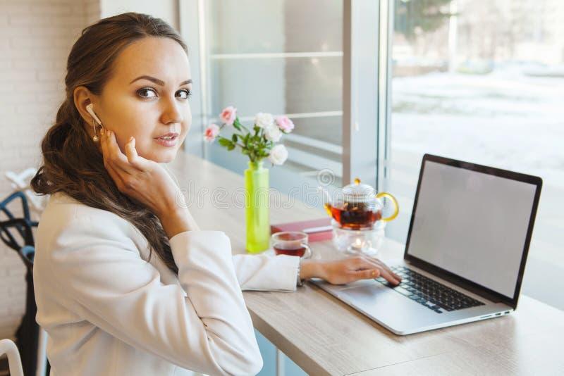 Flicka med telefonhörlurar med mikrofon som arbetar på datoren arkivfoton