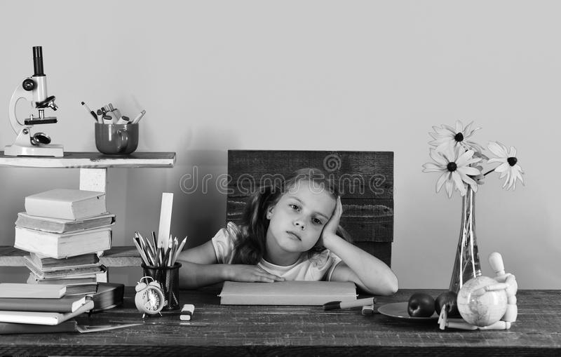 Flicka med trött framsidauttryck Skolflicka med färgrik brevpapper, böcker, jordklotet, klockan och blommor royaltyfri foto