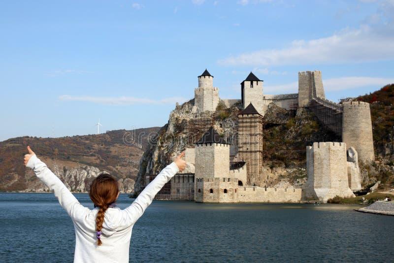 Flicka med tummar upp blickar på den Golubac fästningen på Donau arkivfoton