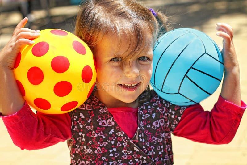 Flicka med två bollar arkivfoto