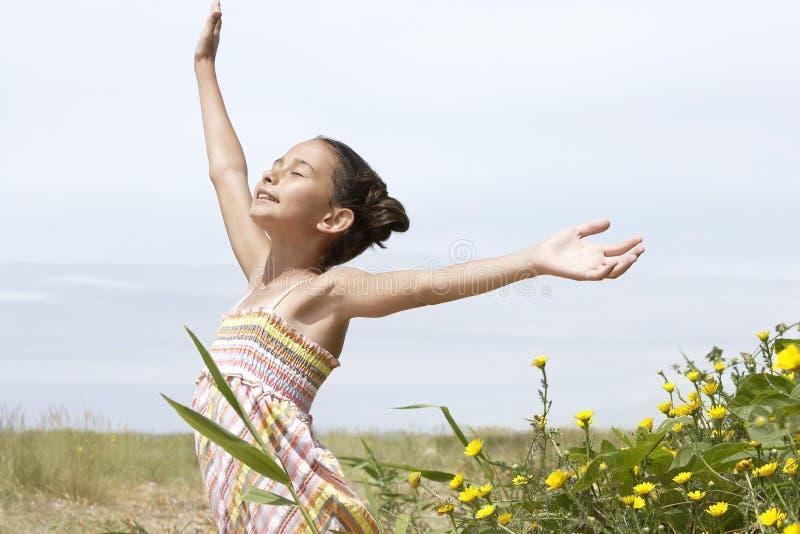 Flicka med utsträckt tyckande om solljus för armar på fältet royaltyfri foto
