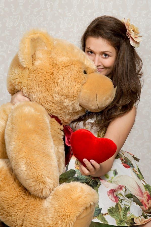 Flicka med välfylld hjärta och björn arkivfoto