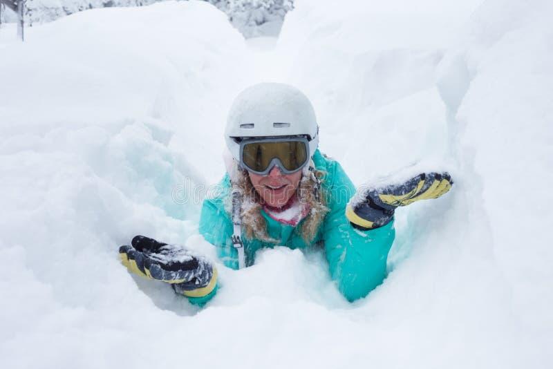 Flicka med vintersportutrustning som lägger i djup snö royaltyfri fotografi