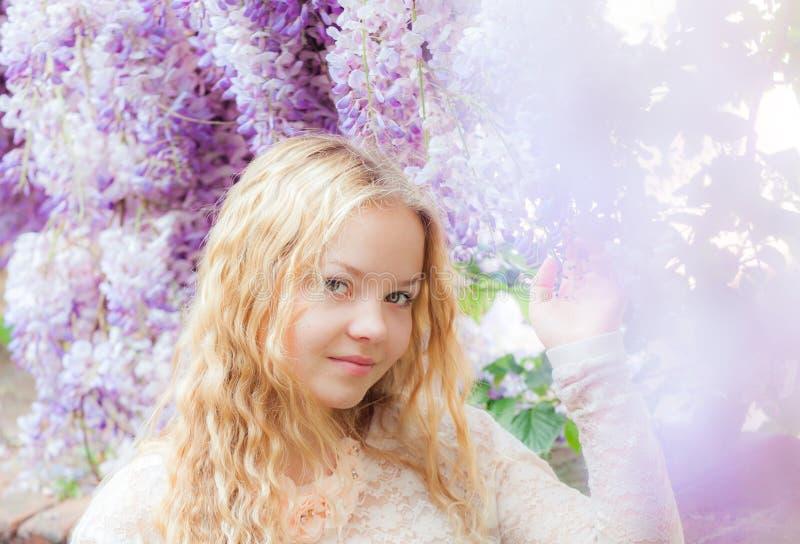Flicka med wisteriablommor arkivbilder