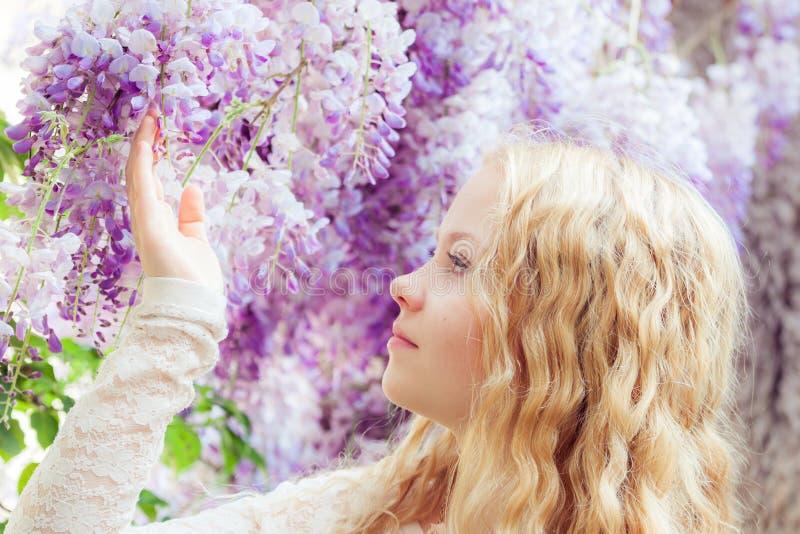 Flicka med wisteriablommor royaltyfria foton