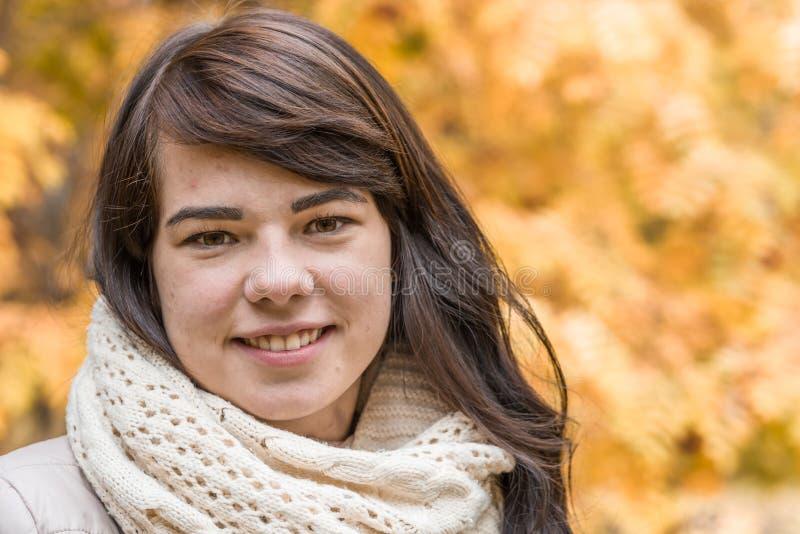 Flicka mot bakgrunden av höstlövverk arkivfoto