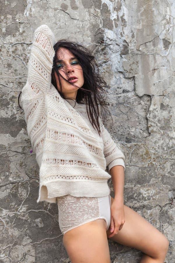 Flicka mot den gamla betongväggen fotografering för bildbyråer