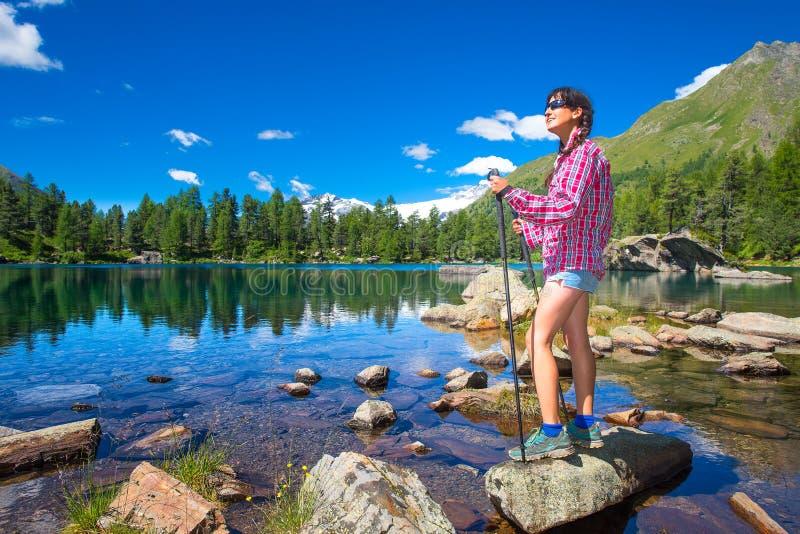 Flicka nära en färgrik bergsjö under ett berg som trekking royaltyfri bild