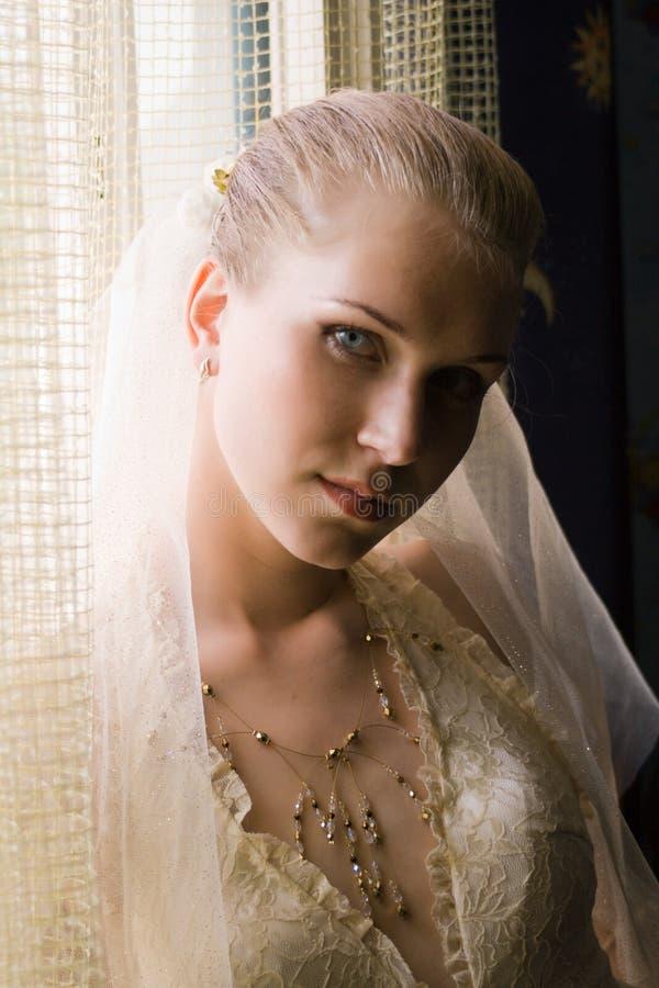flicka nära fönster royaltyfri foto